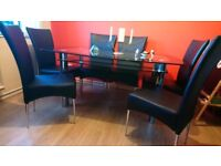 Black boat glass table & 6 black faux leather chairs.
