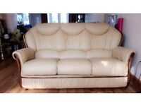 An elegant light butter coloured Lawson sofa, with a leather finish, and rimmed with glossy wood