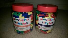 Two tubs of magnetic letters and numbers