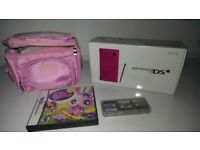 Pink Nintendo DS with carry bag and several games