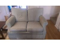Good quality comfy 2 seater sofa witb green & white stripes and wheels