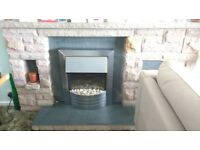 Stone fireplace with grey slate hearth and back panel (electric fire not included)