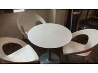 2 circular white breakout tables