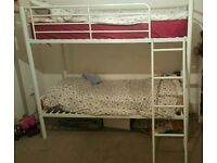 White metal bunk bed with mattresses
