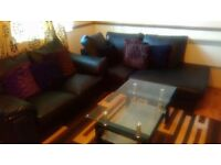 Two black sofas with coffee table and cushions