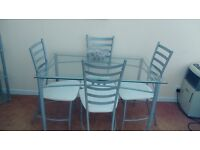 LOVELY GLASS TABLE AND FOUR CHAIRS FOR SALE IN GOOD CONDITION