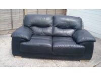 2 Seater black faux sofa in good condition ,buyer collects.