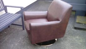 This is a swivel arm chair made by Next in a leatherette material in good condition
