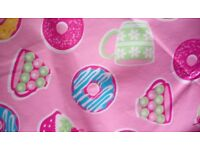 Circular wipe clean tablecloth with special fabric backing and pink and cupcake design