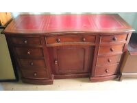 Antique mahogany kneehole desk with red leather top.