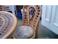 Cane table and 4 chairs. Glass top table