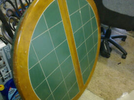 Extending dining table with green tiled top.