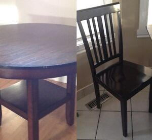 Round solid wood table and 4 wooden chairs.