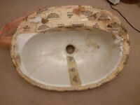 unused counter sunk ceramic bathroom sink or wash hand basin two tap holes