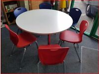 WHITE ROUND TABLE ON 4 CHROME LEGS AND 6 RED OR BLUE CHAIRS