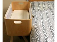 Crib next to bed with incline and bag for easy storage