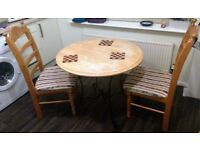 A strong solid wood Dining table with 2 cushioned chairs