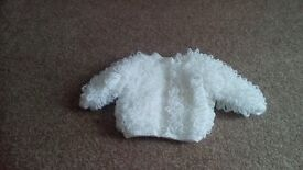 Hand knitted baby jacket and hat.