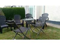 4 plastic garden chairs and glass top bistro table with 2 chairs