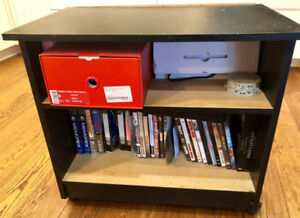 Black TV stand with one shelf, has wheels.