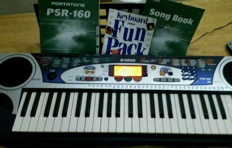 Yamaha electronic keyboard complete with charger and music booklet