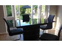 Black glass table and 4 leather look dining chairs
