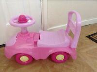 Girls sit on or push car