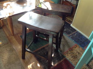 TWO solid wood espresso saddle stools