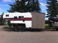 Truck camper  on flat deck trailer.