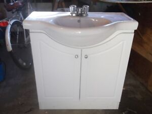 Narrow white bathroom vanity with sink and faucets