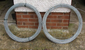 Two coils of galvanised fencing wire