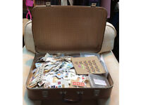 Job lot of loose postage stamps from around the world in a vintage suitcase