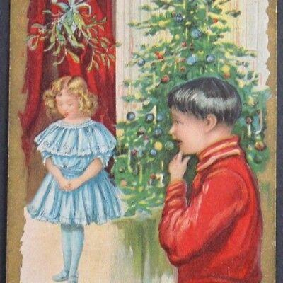 C.1900 Postcard Christmas Best Wishes Girl Mistletoe Boy Looking Tree Cute