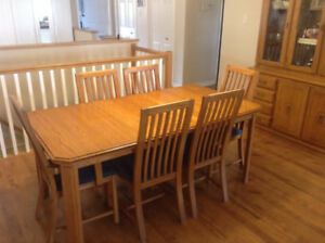 Best offer. Solid oak dining room table, 6 chairs and hutch