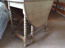 Oak gate legged table dipped revealing light wood.