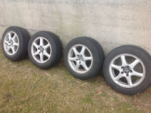 Set of 15 inch aluminum Volvo rims with tires.