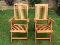 Wooden reclining garden chairs.