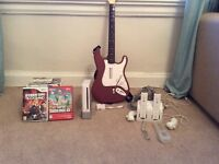 Wii w/ 14 games, charge kit, rock band guitar and game, 2x remotes and remote protector