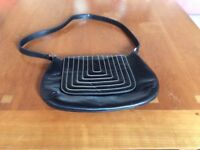 Black leather handbag with white stitching detail