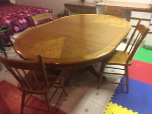 Round extendable pedestal table and four solid oak chairs.