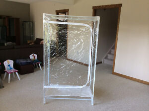 Portable clear plastic wardrobe with wheels.