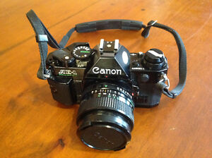 Canon AE-1 Program 35mm reflex camera set with FD lenses, tripod