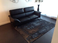 Unique imported black Italian leather couch with flip down back