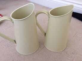 Two cream metal jugs
