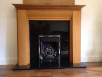 Contemporary Black Granite fireplace with wooden surround and gas real flame fire