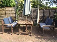 Wooden table chairs and umbrella