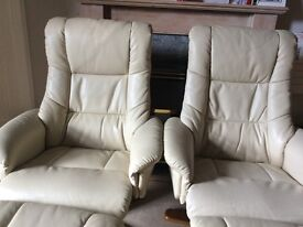Cream leather recliners with footrests.