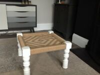 Footstool with white wooden legs and woven top