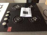 Culina 4 burner on black glass gas hob.