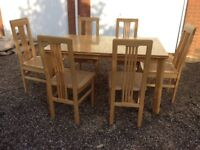 Light wood table with 6 chairs. Possibly Mango Wood Lloyd loom seats